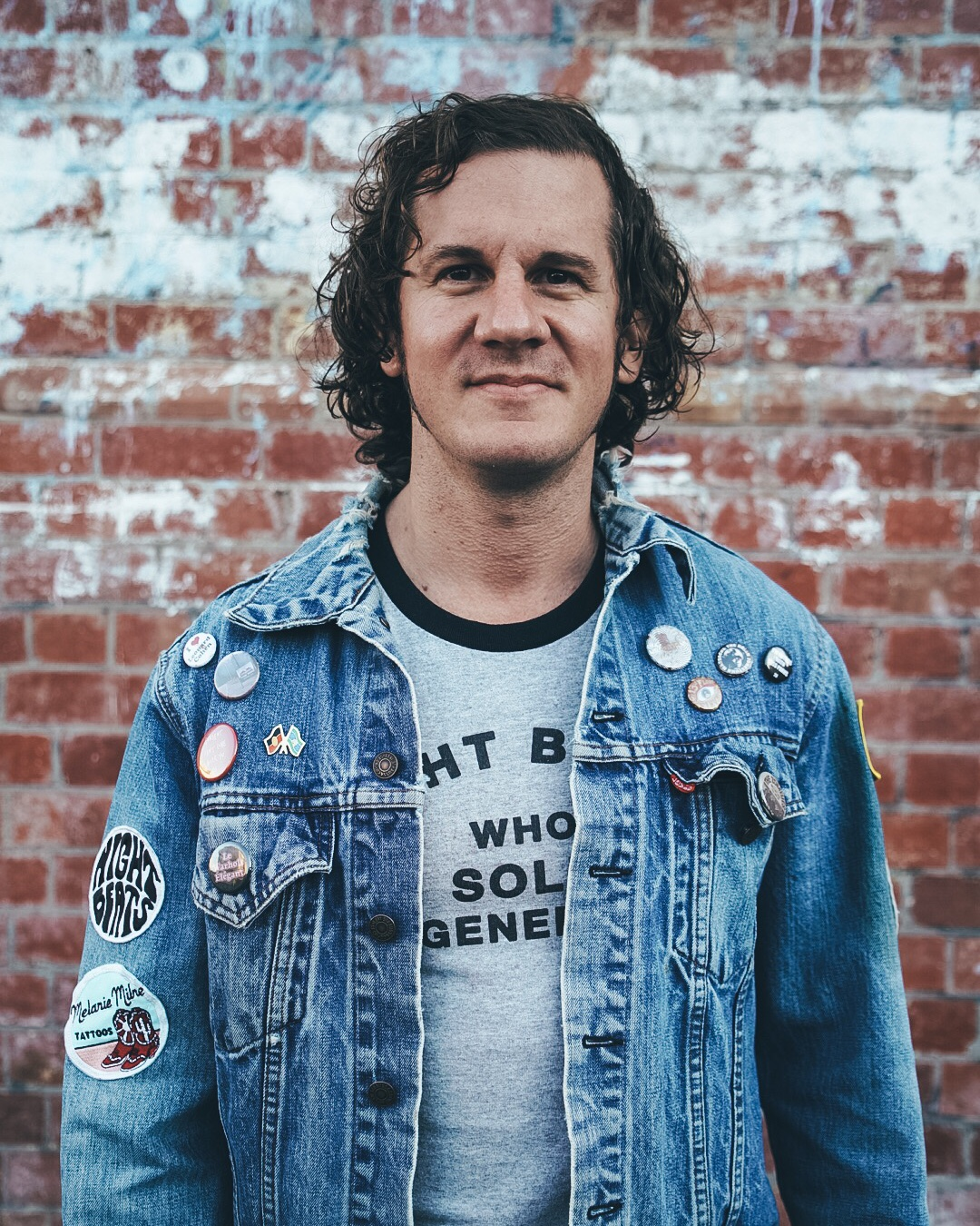 David Couri, new Executive Manager of Octapod, photographed in a t-shirt and denim jacket covered with buttons and patches.