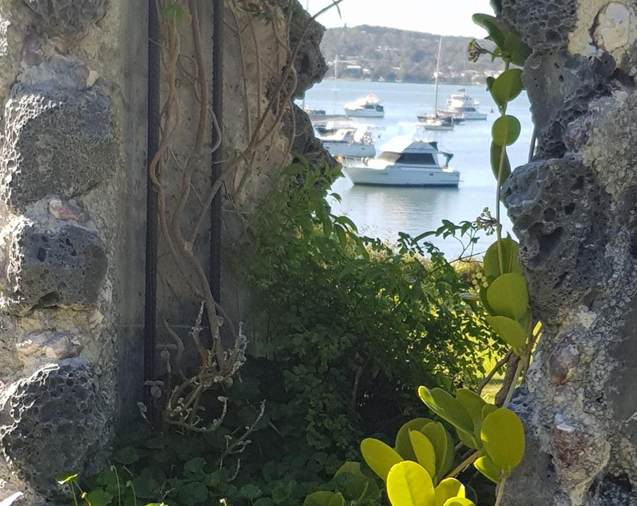 A view through a hole in a stone wall. Steel beams are visible in the wall construct, and green plants are growing through. A body of water with a boat can be seen through the hole.